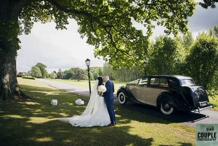 The newlyweds stop off in the driveway of Cabra for a photo with the old tree and their vintage wedding car. Weddings at Cabra Castle photographed by Couple Photography.