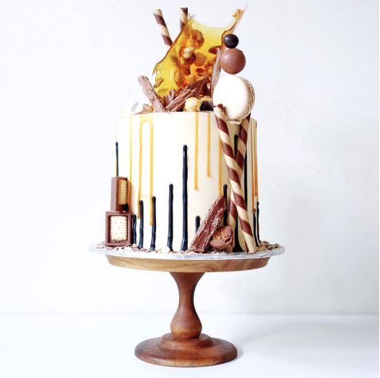 Layers of vanilla cake with salted caramel buttercream, upside-down drip, salted caramel drip, toffee and mixed nuts sail, peanut butter Lindt balls, Mars bar brownie, broken up flakes, salted caramel popcorn and loads of dark chocolate covered maltesers Cakes by Cliff in Sydney, Australia
