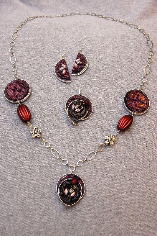 Kette, Ohrringe und Anhänger aus Nespresso Kapseln in weinrot und braun, mit Perlen und aufwändingen Applikationen.