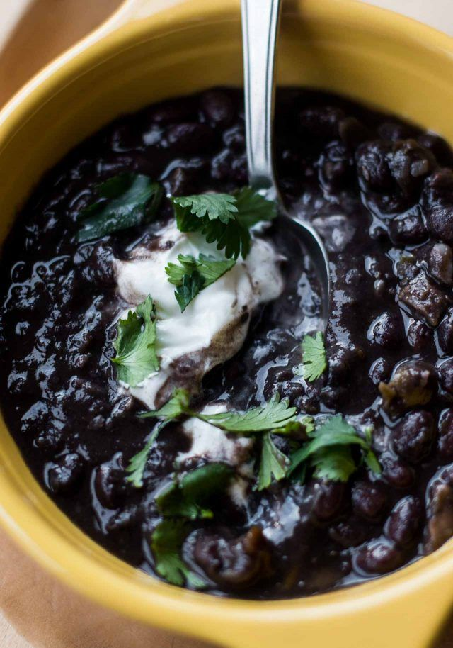 A hearty black bean soup recipe, perfect for warming up, with a touch of spice and cool sour cream!
