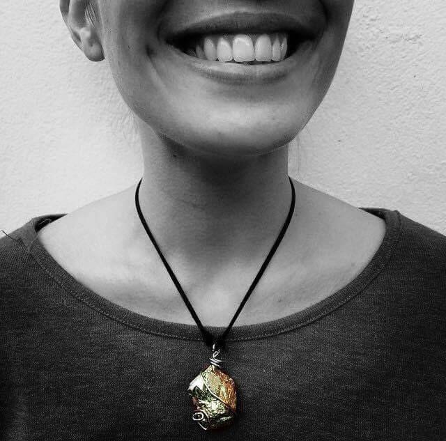 collar de piedra color plateada/dorada con cuerda de gamuza en color negro.