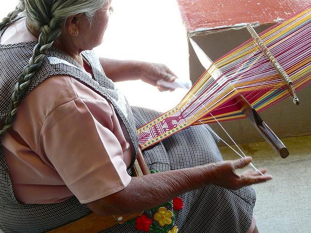 Woman weaving on a backstrap loom in Oaxaca, Mexico.