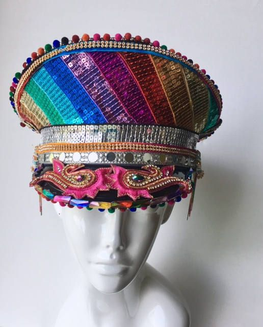 This absolutely stunning Military Captain hat has been painstakingly embellished with trims, beads, pompoms, fringe, mirrors and embroideries. I am extremely proud of this piece, some of the beads and gems used are color shifting and you will find some fun movement with the rainbow fringe.  Absolutely one of a kind and a collectors piece  In the image the hat is placed askew in some shots, making it look lopsided. This is not the case! The hat is perfectly symmetrical , as are the…