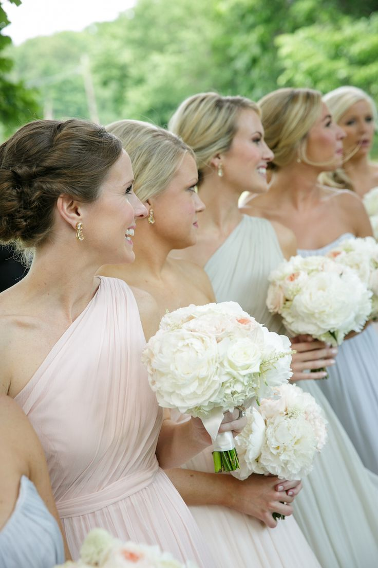 Bridesmaids wore one-shoulder, pastel dresses & carried ivory bouquets. Photography: Karlisch Studio Read More: http://www.insideweddings.com/weddings/southern-chic-wedding-in-oklahoma-with-performance-by-boyz-ii-men/697/