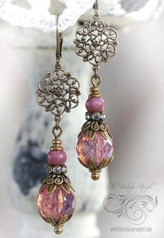 Victorian inspired and delicate and detailed, these beauties feature brass filigree and Czech glass pink opal beads. Aged brass filigree flowers suspend the drop assembly crafted from pink opal Czech glass faceted rounds (12mm) and smaller rose colored gemstone rounds with ornate bead caps. A rhinestone rondelle adds just a pop of elegance. Hung from leverback hooks in aged brass for pierced ears. All components are American-made brass, free of lead and nickel About 2.5