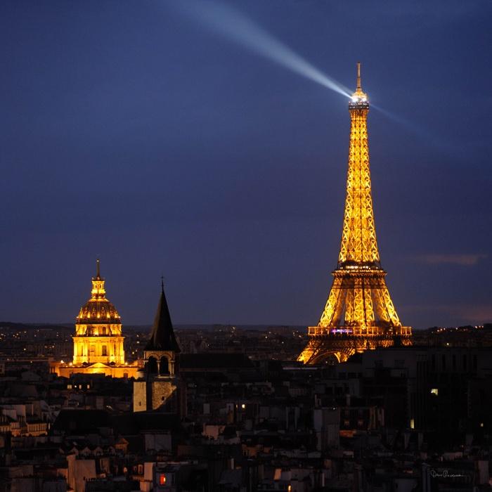 France - Paris - Tour Eiffel, en arrière-plan, le dôme éclairé des Invalides.  Dans l'ombre,le clocher de l'église Saint Germain.     Photo de Denis Reverseau