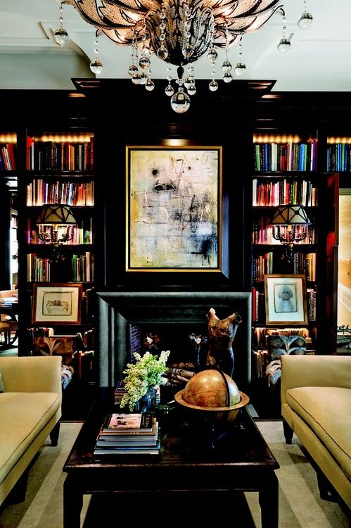 Black walls, chandelier, facing couches, unique sconces, colorful books