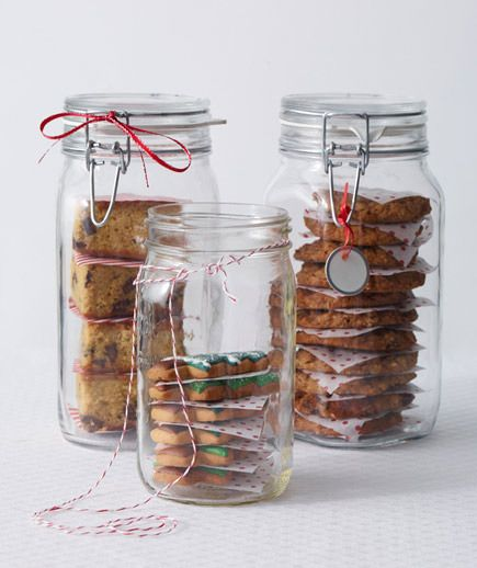Mason jars with cookies and decorative paper separating the cookies.