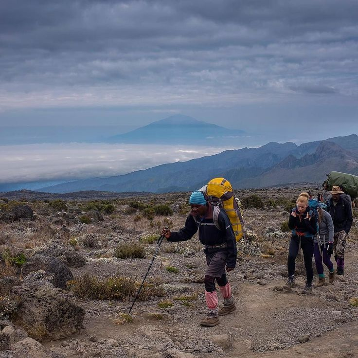 Another shot of Mount Meru with a few of our group led by one our head guides. #kilimanjaro #mountains #tanzania #sunset #love #africa #trekking #sky #clouds #storm #sunset