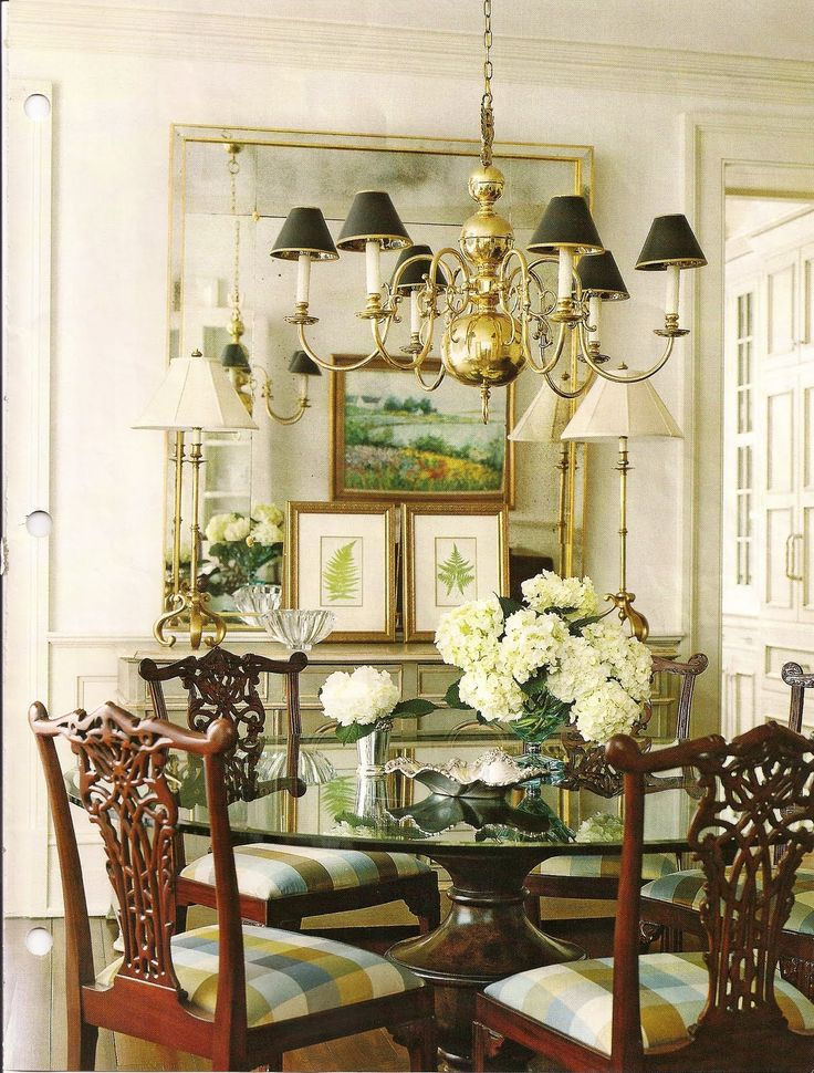 Pretty transitional dining room. The art reflected in the mirror is attractive & I like the traditional chandelier with the sophisticated black shades. The Chippendale chairs are also traditional, but the glass table top makes the space less formal.