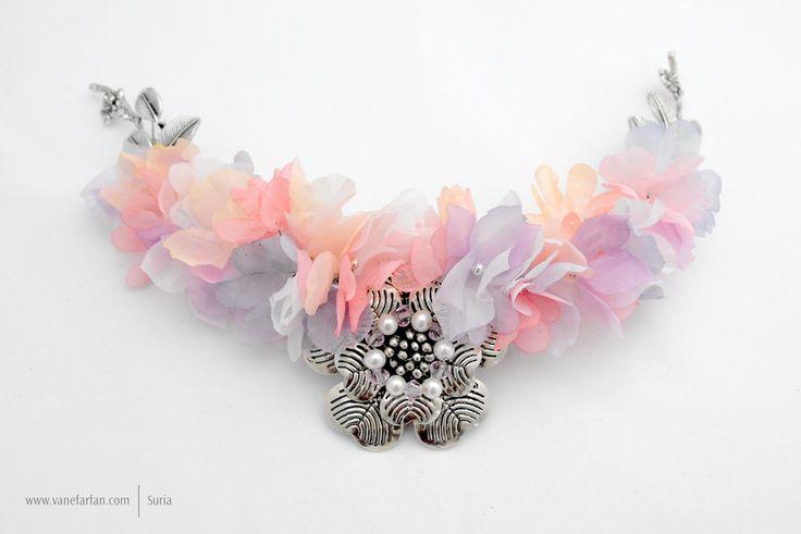 Tocado de flores de gasa con centro de aplique plateado con cristales y perlas.