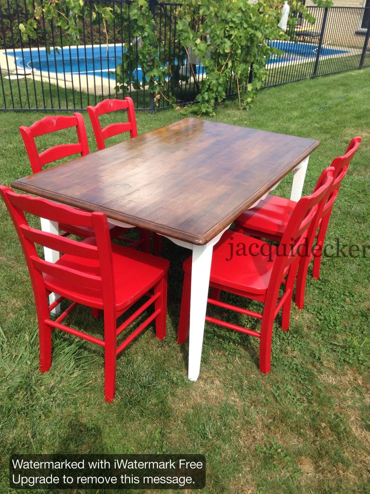 A bright facelift for a previously dull dining table and chairs. Red chairs, walnut stained top, white legs.