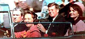 Up front, Texas Governor John Connally and wife Nellie ride with the President and Mrs. Kennedy through downtown Dallas.