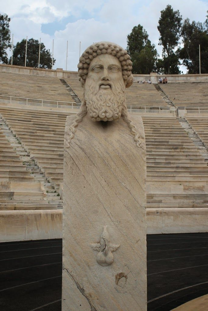 """There are two herms--one on either side of the field. Herms are sculptures that are just under five feet tall, usually made of marble or bronze. The pillar portion of the herm is called the """"shaft,"""" The shaft carries the head of the Greek god Hermes and has a phallic symbol on the front and down just below the center of it—a perfect frieze of a penis and balls... with wings. The Panatheniac Stadium in Athens--chapter 69"""