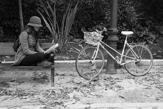 En un banco del Retiro, leyendo junto a la bici.
