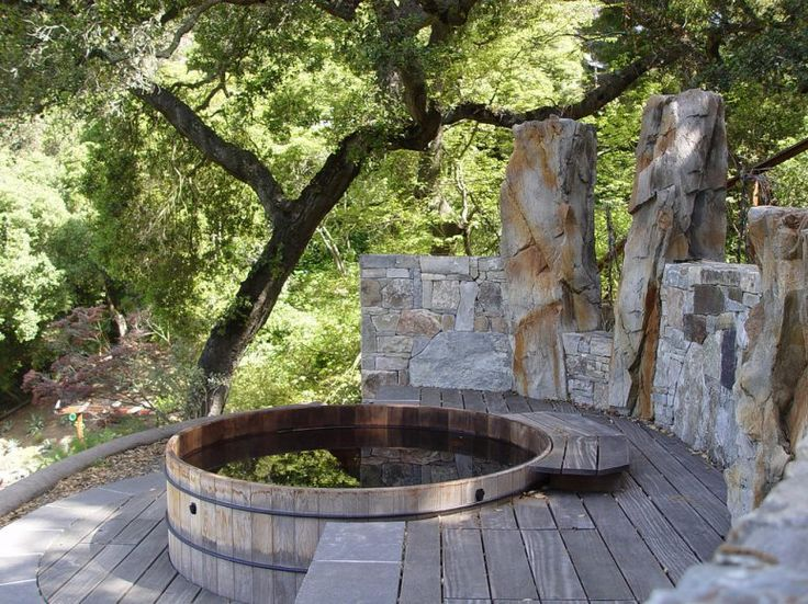 this rustic deck is a great example of how well a stone wall match a redwood hot tub tucked among the tree