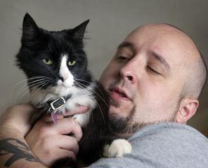 Will Braden holds Henri, the cat who stars in Braden's videos.