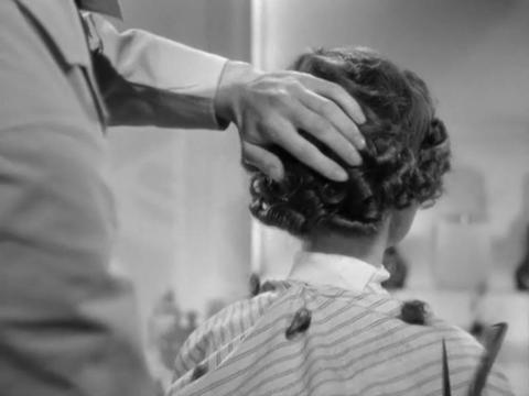 Eng gedrehte Locken, und trotzdem deutlich über dem Kragen abgeschnitten. Das Foto stammt vermutlich aus den 1960er Jahren. Ein moderner Bob ist hinten kürzer geschnitten, sieht aber nicht so streng aus.