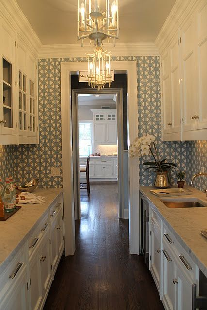 Easy way to improve an old galley kitchen: update lighting, drawer pulls, cabinet knobs and add wall paper...awesome!