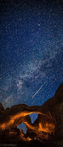 Meteor streaking over the lightpainted double arch in Arches National Park, United States