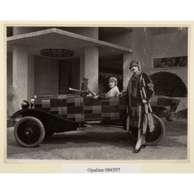 Sonia Delaunay is wearing patterned suit of her own design standing next to Citroen B12 decorated by her with the same pattern.  -- Studio REP Modèles devant voiture simultanée, 1925