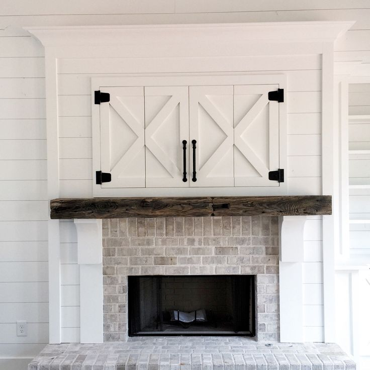 Rustic farmhouse fireplace in white, brick, and rustic wood
