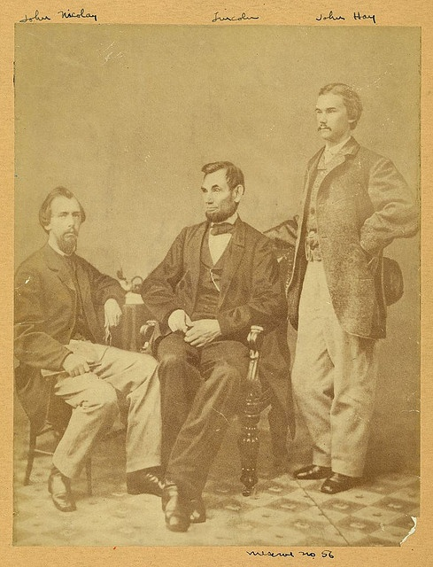 """President Abraham Lincoln seated between his private secretaries John G. Nicolay and John Hay at a photo session in Alexander Gardner's studio in Washington, D.C., on November 8, 1863.  """"On this day John Hay wrote in his diary: 'Went with Mrs. Ames to Gardner's Gallery & were soon joined by Nico (John G. Nicolay) and the Prest. We had a great many pictures taken ... some of the Prest. the best I have seen. ... Nico & I immortalized ourselves by having ourselves done in a group with the…"""