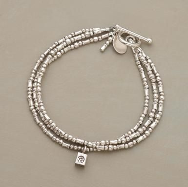 "Strands of sterling silver beads jingle on the wrist. One dangles a flower-stamped cube. Toggle clasp. Handmade in USA exclusively for us. 7-1/2""L."