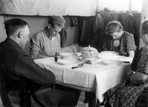 Bidden voor de maaltijd, Wieringermeer 1940. Twee vrouwen en twee mannen in gebed voor de gedekte tafel, waarop een soepterrine, soepborden en een maggiflesje staan.