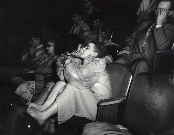young couple kissing in a dark movie theatre...talk about a kiss curling your toes....lol :)