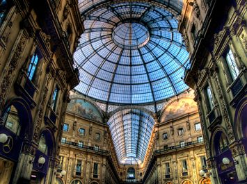 S4E1: Galleria Vittorio Emanuele II, Milan. The famed Galleria Vittorio Emanuele II is a magnificent five story arcade covered with a glass and iron roof. The 19th century structure is decorated with patriotic mosaics and statues.