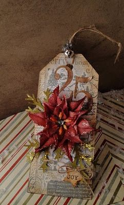 Wow, Rustic, steampunk ish tag. Stamped. Brown background. Gold ish green branches toped with and amazing Christmas red flower. Rope tied start on.