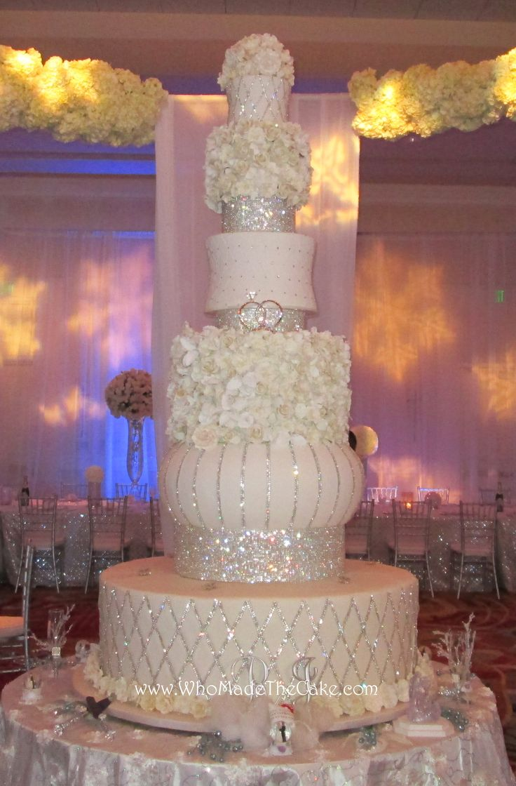 """This towering cake is over 7' tall with a 46"""" wide base. Accented with yards of bling & hundreds of sugar flowers, this is sure to be a focal point at any reception. By www.WhoMadeTheCake.com"""