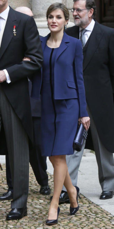 Doña Letizia escogió un look formado por vestido en doble crêpe en lana azul marino con cinta de terciopelo azul noche y chaqueta entallada a juego. La esposa de Felipe VI estrenó el conjunto en el Día de la Hispanidad en octubre de 2015.