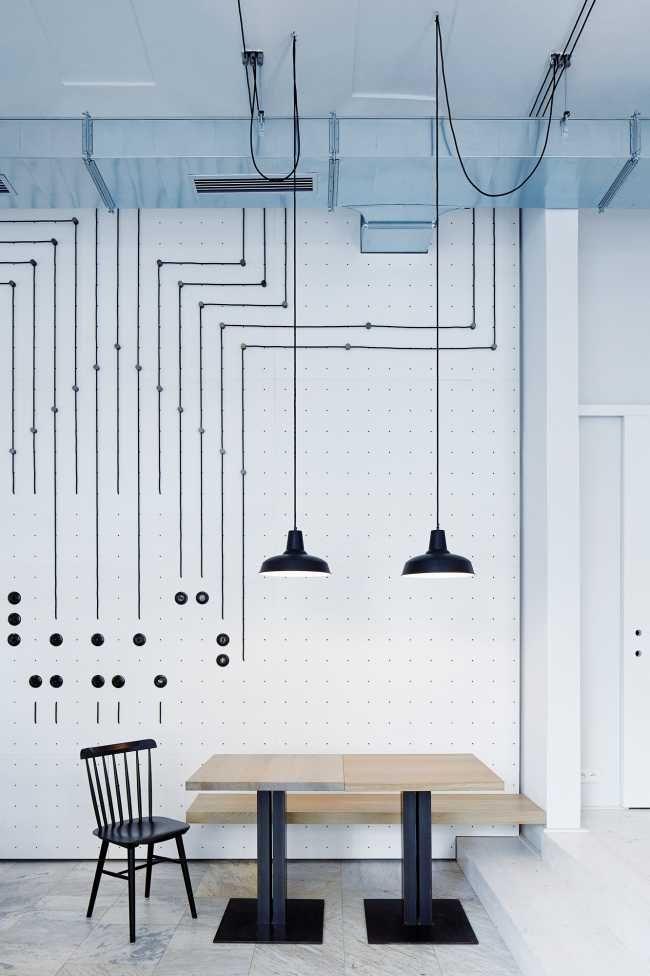 Sieť drôtov rozbiehajúca sa od spínačov za pultom k svetlám nad stolmi zviditeľňuje prepojenie medzi obsluhou a hosťami.