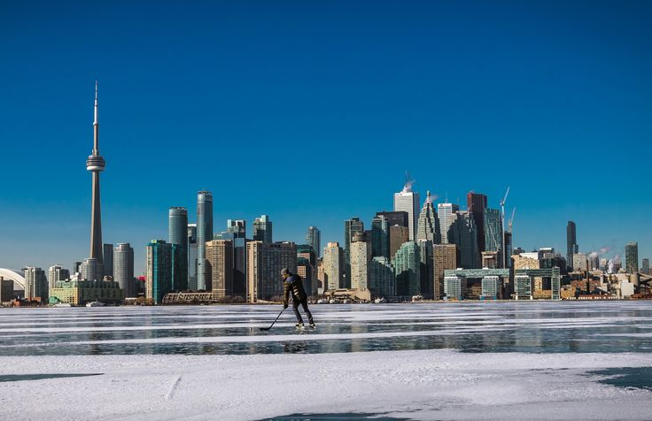 Toronto in the winter with an ice hockey player skating on Lake Ontario