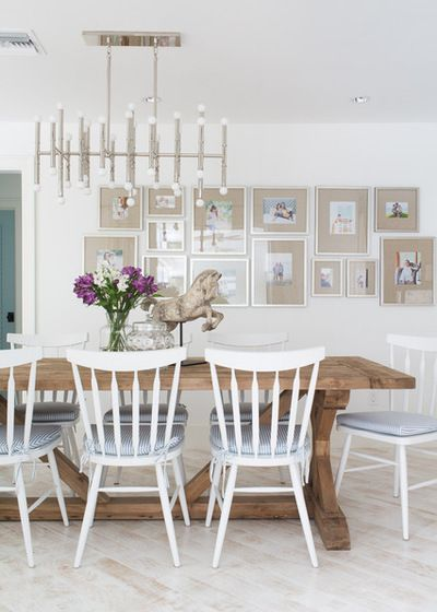 Beach style dining room with a reclaimed wooden table, classic white dining chairs and a wall of framed photographs | Lischkoff Design Planning