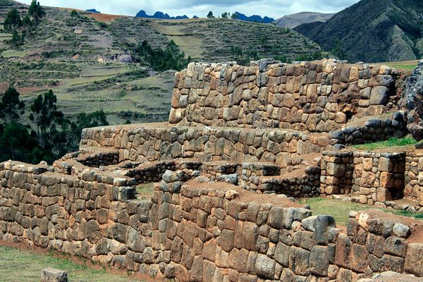 Sunlight upon the limestone construction of the Inca Empire - Chinchero Ruins - here among the Cordillera Vilcanota - with the jagged cloud-shaded peaks of the Cordillera Urubamba along the distal horizon - Cusco department.