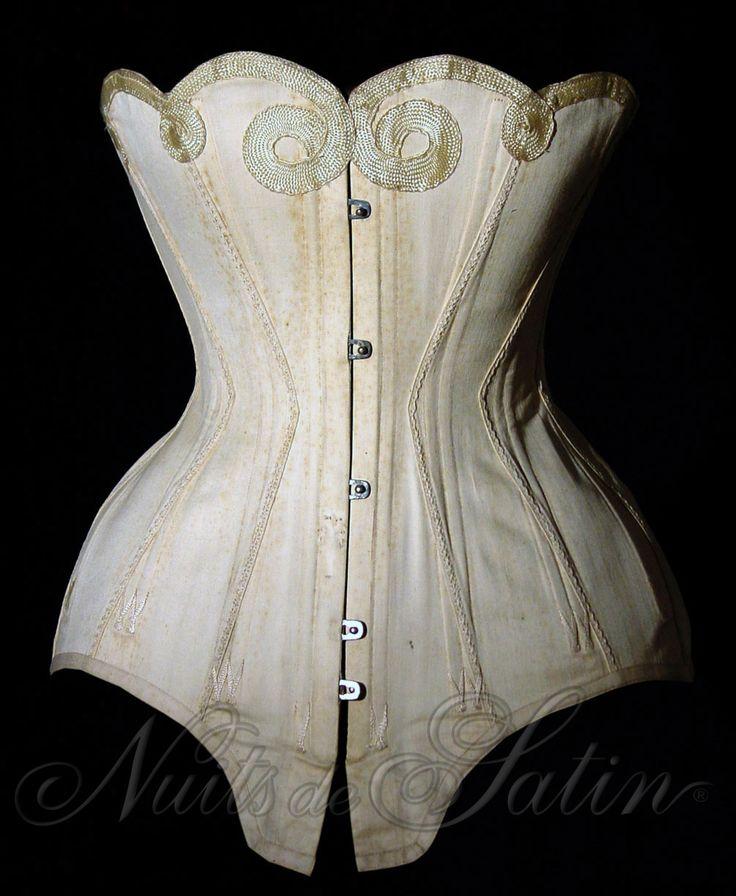 """Corset de marque"""" L'ABEILLE"""" modèle """"New Style"""" 1901 en coutil beige de marque , fabriqué à Barcelone, évantaillé et brodé de soie ivoire, le haut du corset est découpé en corolle et orné d'une ganse en soie ivoire, baleinage extra Ariston, avec son étiquette publicitaire d'origine et comportant 22 baleines - Busc de 32 cm avec 5 attaches - Tour de taille 55 cm. Collection Nuits de Satin"""