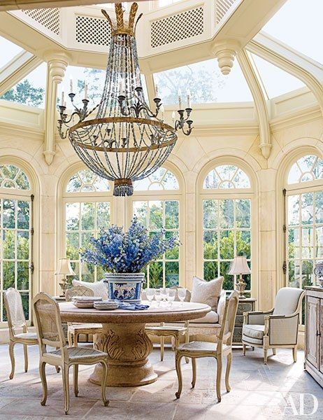 Breakfast is served in this Houston conservatory, which features a 19th-century Italian marble table topped by a grand Italian chandelier.