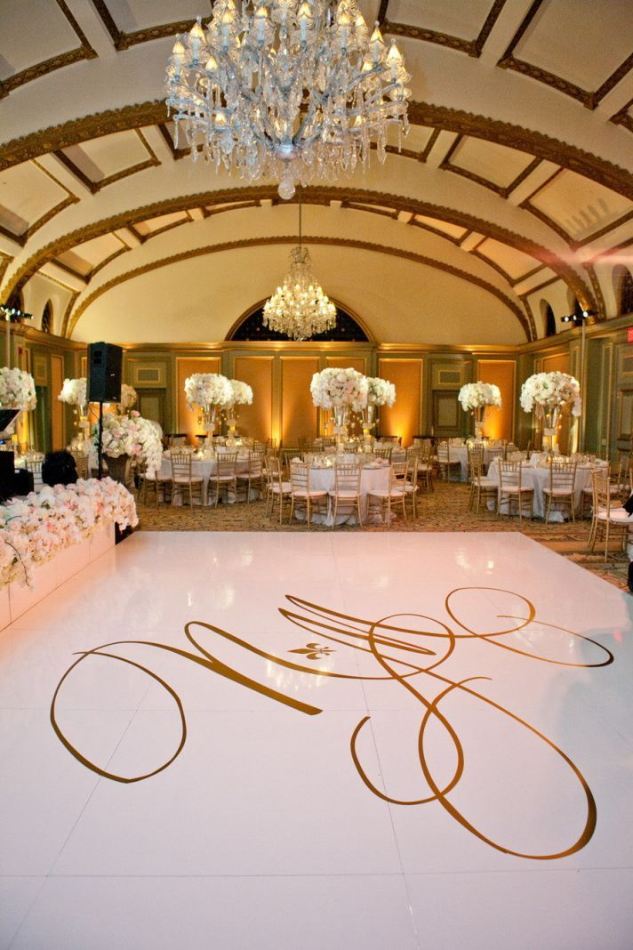 Slick white dance floor with a gilded calligraphy monogram