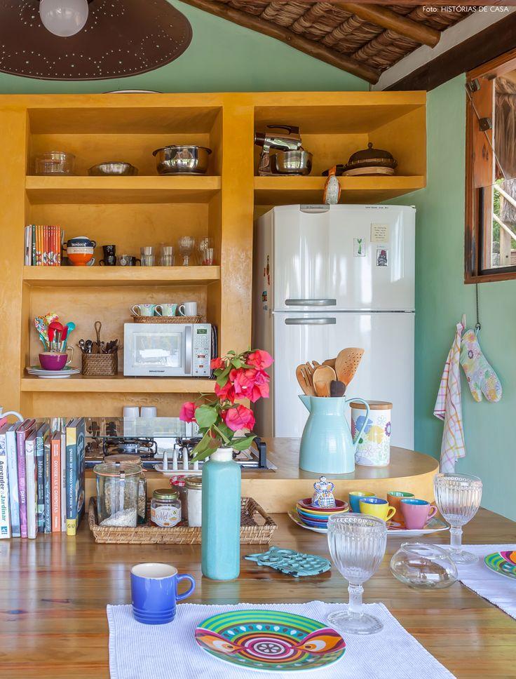 Cozinha com armário aberto de alvenaria pintado de amarelo e bancada de madeira que faz as vezes de mesa.