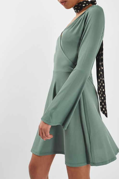 We love the bohemian edge that trumpet sleeves lend to an outfit, emphasised with this cute mini dress. In a green ribbed jersey, it comes in a flattering wrap-style with a skater skirt. Team with black biker boots for an added edge. #Topshop