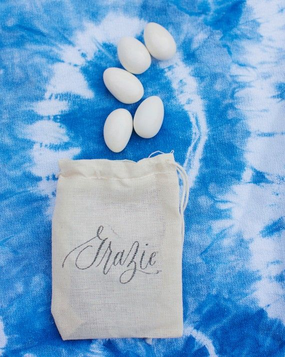 """If you're Italian, it only makes sense to honor the Italian tradition of giving five Jordan almonds (or """"bomboniere"""" as they're known"""") to signify health, wealth, happiness, fertility, and longevity. Though typically a tulle bag is used, this bride and groom opted for a muslin option stamped with """"grazie"""" as a token of thanks for all of the guests."""