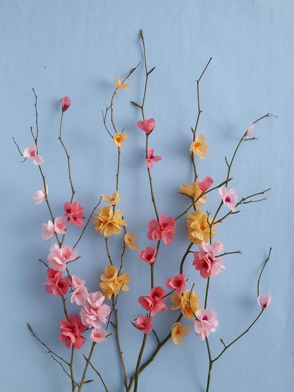 Papercraft. DIY Paper Blossom attached to branches on blue background