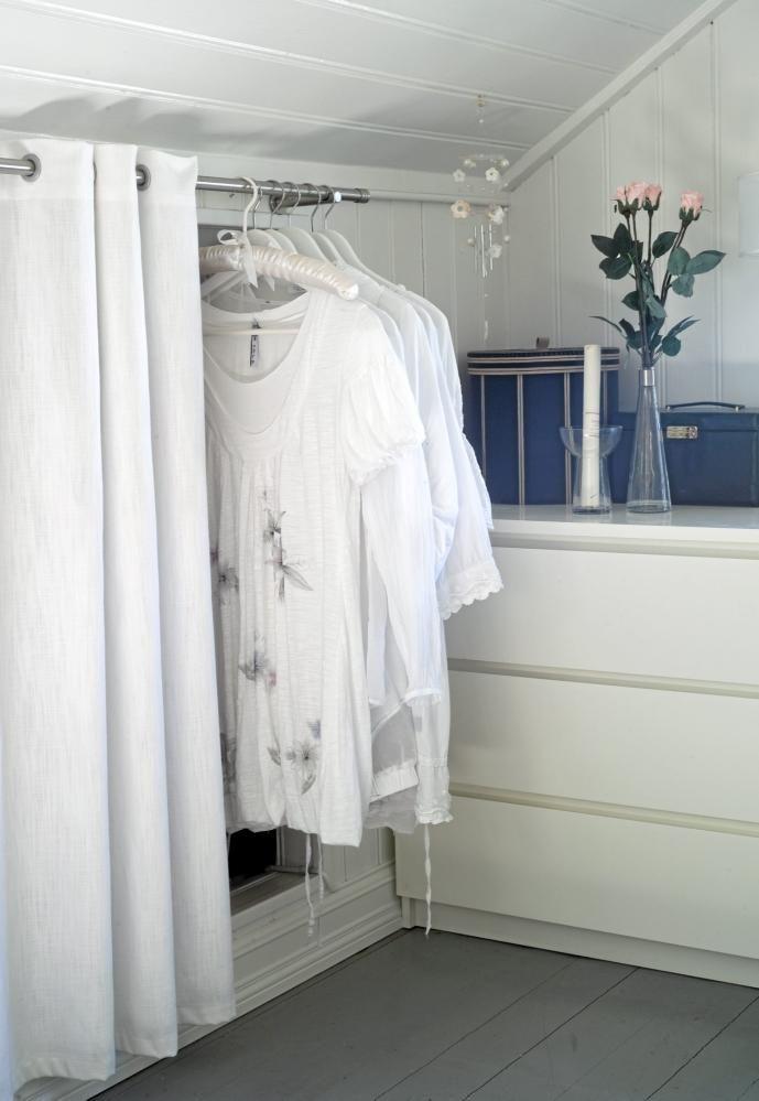 Rommet er gjennomført hvitt slik at enkle detaljer skiller seg mer ut. Hvite gardiner skjuler et lite hulrom i veggen, og på gardinstangen henger også hvite skjorter og sommerkjoler som en del av innredningen.