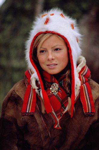 Portrait of pretty Sami girl in a traditional hat and peske at the Jokkmokk Winter Market. Sweden