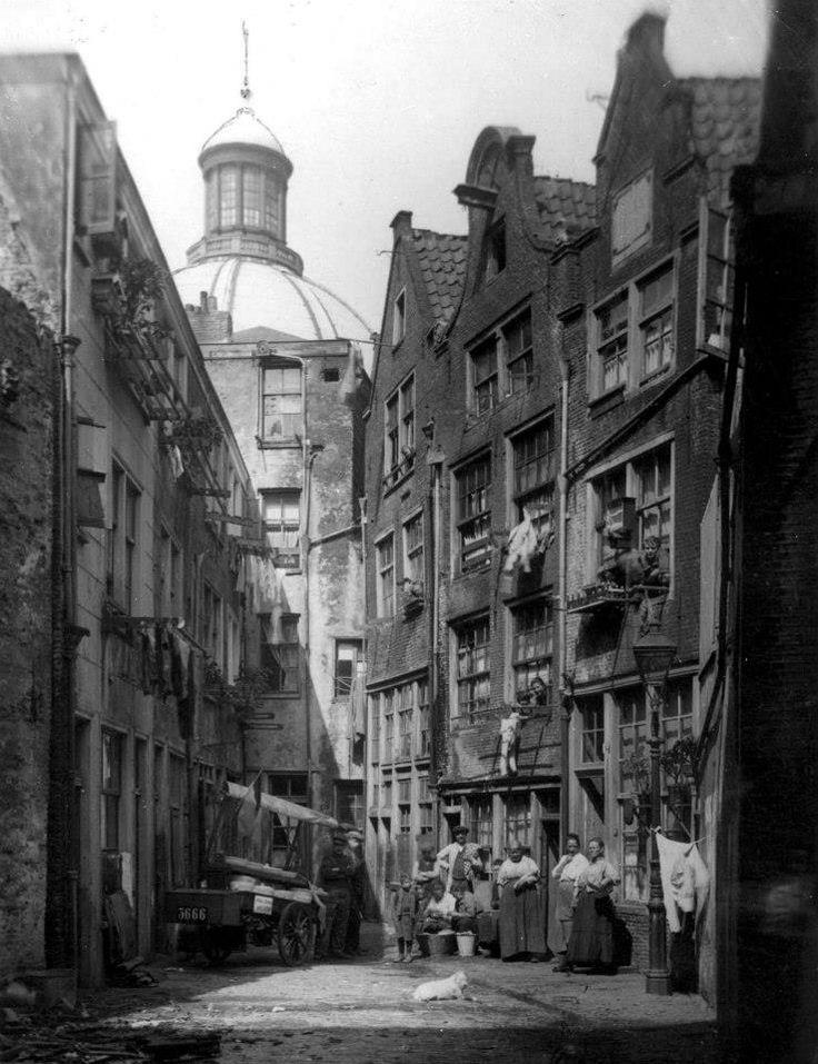 1921 Mensen op straat in een buurt in Amsterdam met krotwoningen. Op de achtergrond de ronde Lutherse kerk