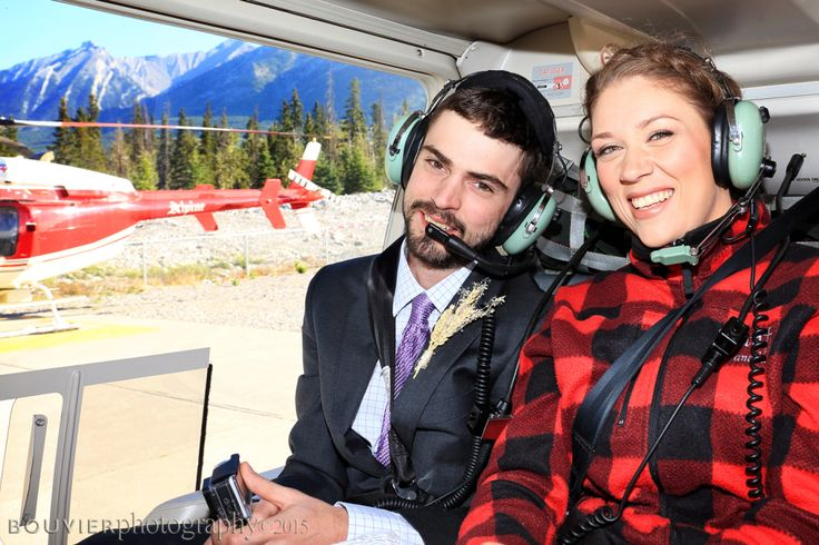 Bride and groom ready to take flight in the helicopter to fly up to the mountain top for their wedding ceremony in Canmore Alberta. Summer heli-wedding. Alpine heli-wedding.