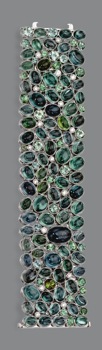 TOURMALINE AND DIAMOND BRACELET.  The wide band clustered with multi-colored round and cabochon oval tourmalines in graduating shades of green weighing approximately 197.80 carats, further decorated with 17 round diamonds, mounted in 18 karat white gold, length 7 inches.